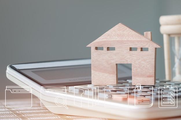 Vastgoedbezit concept: digitale documentbestand marketingpictogrammen op houten huismodel met zandloper. ideeën voor aanbiedingen van investeringen in hypotheken en beheer voor leningsovereenkomsten om een nieuw huis te kopen