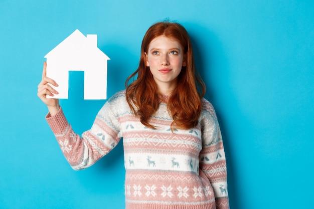 Vastgoedconcept. afbeelding van een schattig roodharig meisje dat nieuwsgierig kijkt naar het papieren huismodel, denkt aan het kopen van onroerend goed, omhoog kijkt naar kopieerruimte, blauwe achtergrond.