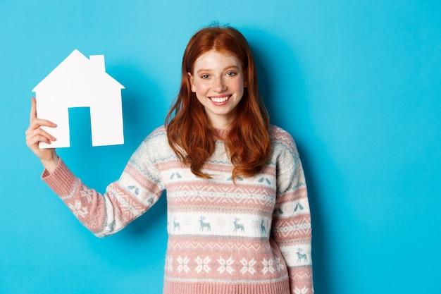 Vastgoedconcept. jonge glimlachende vrouw met rood haar die een papieren huismodel toont, staande over een blauwe achtergrond