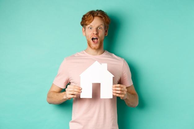 Vastgoedconcept. opgewonden roodharige man met baard, met uitgesneden papieren huis en hijgend van ontzag, gefascineerd naar de camera starend, staande over mint achtergrond