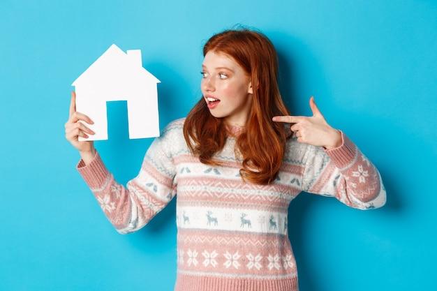 Vastgoedconcept. opgewonden roodharige vrouw met rood haar, wijzend en kijkend naar papieren huismodel, appartementadvertentie tonend, staande over blauwe achtergrond.