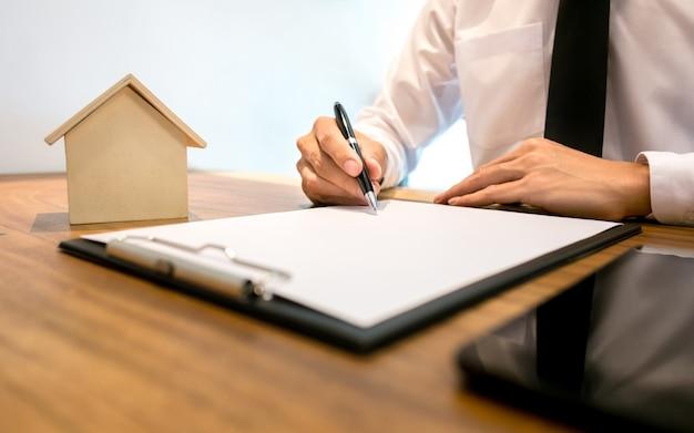 Vastgoedmakelaar met contract handtekening en analyse van de waardering van woning eigendom