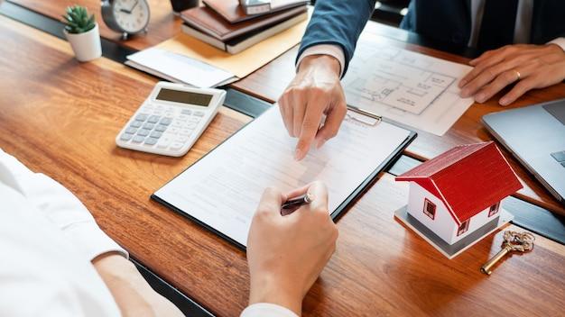 Vastgoedmakelaar of verkoopagent die overleg geeft met de klant over het kopen van een huis
