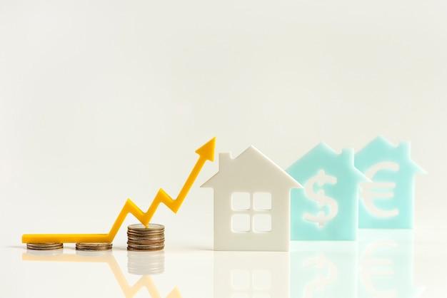 Vastgoedmarkt, grafiek, pijl-omhoog. huismodel en een stapel munten. het concept van inflatie, economische groei, de prijs van verzekeringsdiensten. ruimte kopiëren