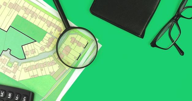 Vastgoedprojectbanner, zoeken perceelconcept, plat leggen en bovenaanzicht plat leggen achtergrondfoto met kadastrale kaart, vergrootglas en glazen om groene kantoortafel