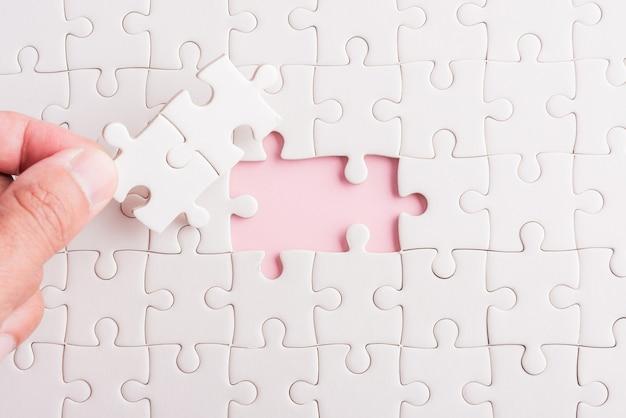 Vasthouden laatste stukje wit papier puzzelspel laatste stukjes zetten