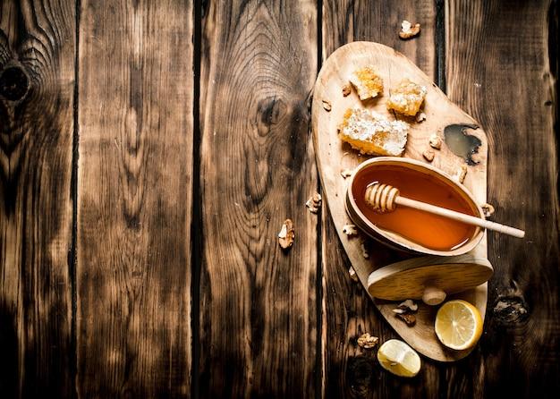 Vat met honing en noten op boomstam. op houten achtergrond.