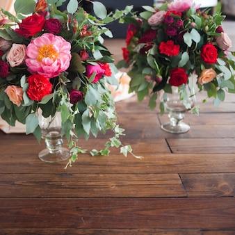 Vazen met boeketten van rode bloemen op de vloer.