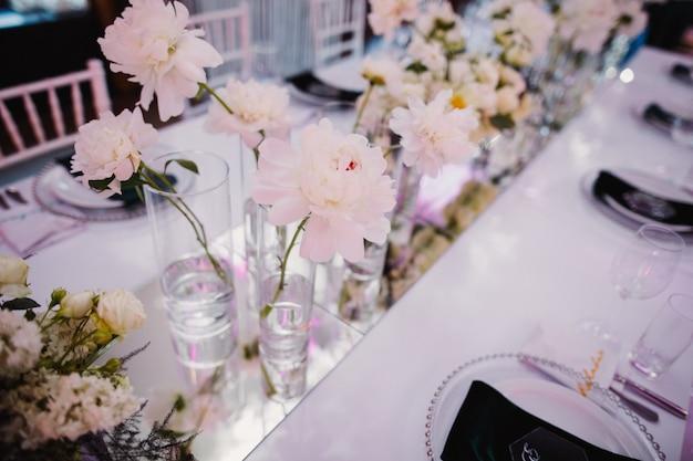 Vazen met pioenrozen op tafel