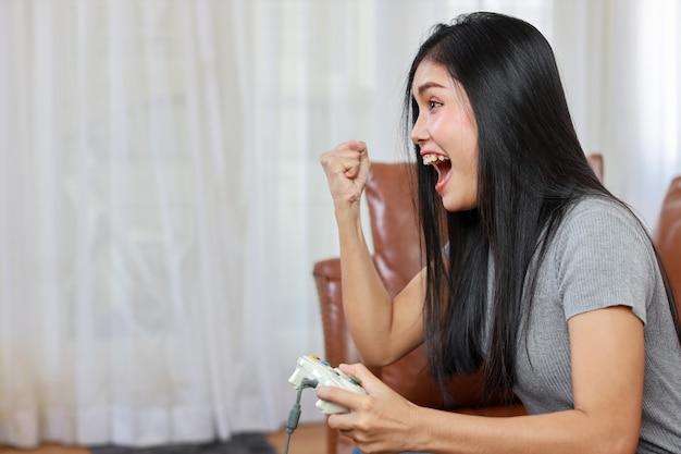 Vdo gameconsole station concept. actieve aziatische vrouw die op de bank zit, joystick vasthoudt en een spannend spel speelt. schattig meisje zag er opgewonden uit met de gamecontrollerconsole