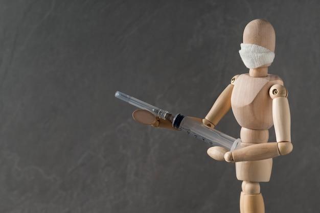 Vecht tegen het coronavirus. houten pop in masker met spuit als soldaat houdt geweer