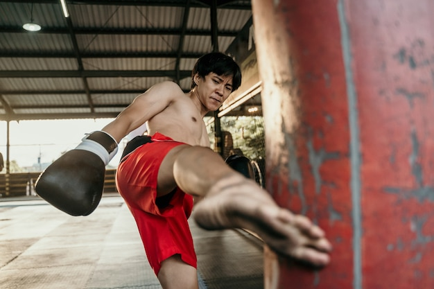 Vechter die enkele trappen oefent met een bokszak in bokskamp