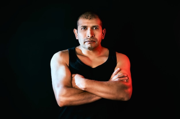 Vechter en sterke man kijken naar de camera en toont zijn gespierde gekruiste armen