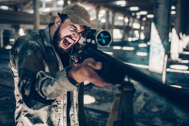 Vechter kijkt door lens op geweer en neemt doel. hij houdt het met beide handen vast. emotionele man schreeuwt en schreeuwt. hij zit alleen in een grote hangar.