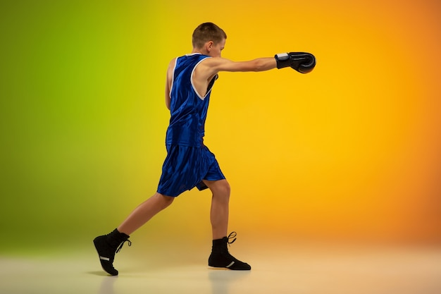Vechter. tiener professionele bokser training in actie, beweging geïsoleerd op verloop achtergrond in neonlicht. schoppen, boksen. concept van sport, beweging, energie en dynamische, gezonde levensstijl.