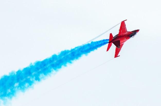 Vechter vliegt in de rook in de aerobatics van de blauwe lucht