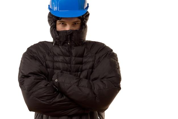 Vechtlustige jonge misdadiger in een zwarte bivakmuts en veiligheidshelm die de weg blokkeert