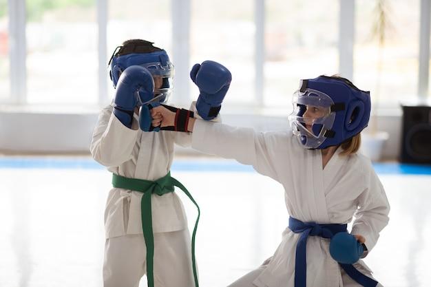 Vechtsport samen. jongen en meisje met witte kimono en beschermende helmen die samen vechtsport beoefenen
