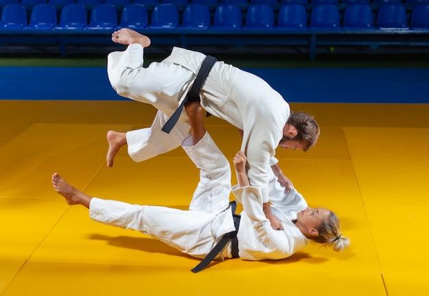 Vechtsporten. sparen portners. sport man en vrouw in witte kimono trein judo gooit en vangt in de sporthal