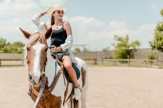 Veedrijfster die een paard berijdt op een boerderij