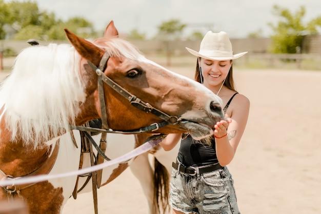 Veedrijfster die haar paard op een landbouwbedrijf voedt