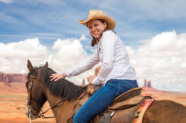 Veedrijfster die strohoed het berijden paard in monumentenvallei draagt