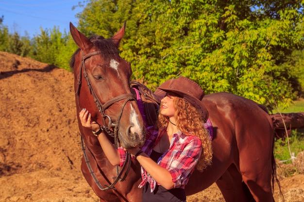 Veedrijfstermeisje het stellen met paard in openlucht portret
