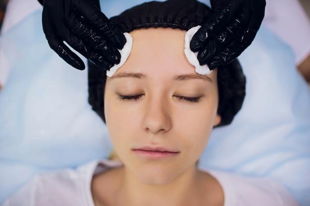 Veeg af met steriel servetgezicht. jonge vrouw die behandelingen in schoonheidssalons ontvangt.