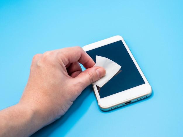 Veeg het smartphonescherm af met een alcoholdoekje om stof en ziektekiemen te verwijderen om besmetting te voorkomen. hygiëne en gezondheidszorg concept.