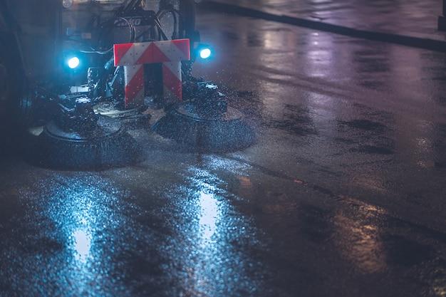 Veegmachines in regenachtige nacht