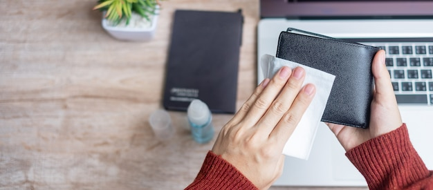 Veegt de vrouwen schoonmakende portefeuille met nat af en ontsmettingsmiddel