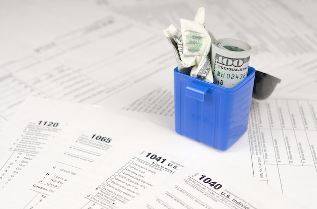 Veel amerikaanse belasting lege formulieren en verfrommeld honderd dollar biljetten in prullenbak
