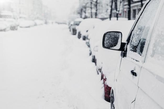 Veel auto's op de winterweg of op parkeerplaats. besneeuwde stad. sneeuwval in de winter
