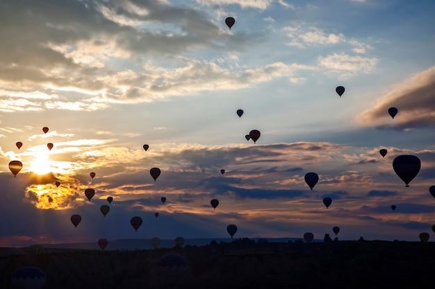 Veel ballonnen met mensen die in de ochtendhemel vliegen in cappadocië