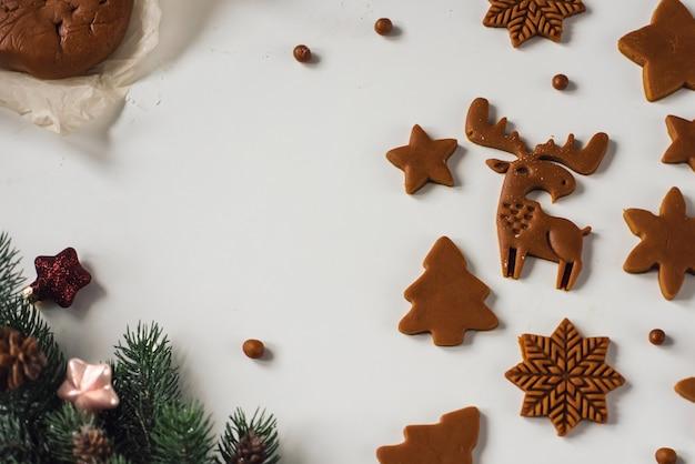 Veel blanco peperkoekkoekjes van verschillende vormen op tafel met kerstdecor