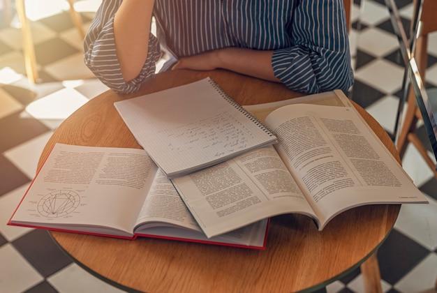 Veel boeken op een houten bureau in een modern café of bibliotheekconcept van onderzoek en het zoeken naar antwoorden in tex...