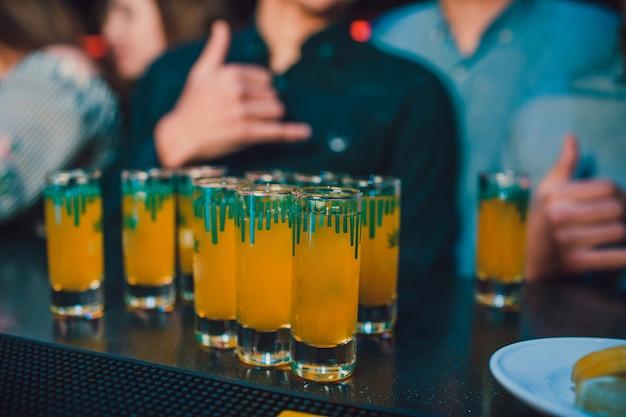 Veel borrelglaasjes met alcohol en citrusvruchtensap.