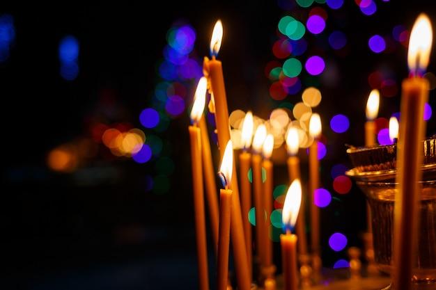 Veel brandende kaarsen staan in een gouden standaard in de kerk. selectieve focus