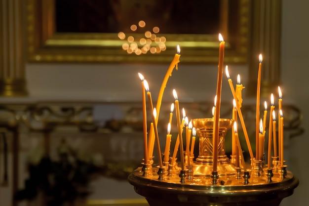 Veel brandende waskaarsen in de orthodoxe kerk of tempel voor ceremonie pasen