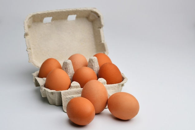 Veel bruine eieren geïsoleerd op witte kippeneieren zijn vers in een kartonnen verpakking