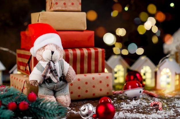 Veel cadeaus in inpakpapier en zelfgemaakt peperkoekhuis, lichten bokeh op