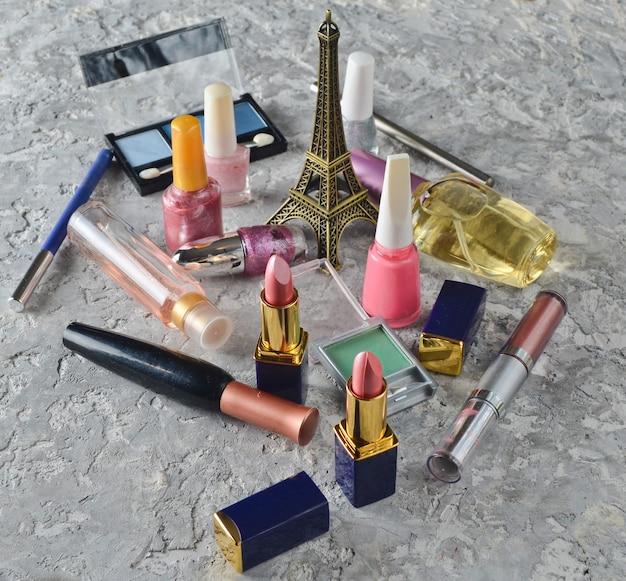 Veel damescosmetica voor make-up en schoonheidsverzorging. nagellak, parfumfles, make-upschaduwen, lippenstift, een beeldje van de eiffeltoren.