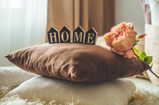 Veel decoratieve knusse kussens en het opschrift home. in het interieur op het bed met een rieten mand en bloemen erin. lente in het interieur. thuis concept