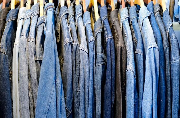 Veel denimoverhemden of jassen die van dichtbij aan hangers in de winkel hangen