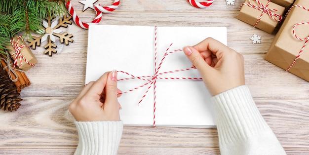 Veel enveloppen vastgebonden met touw. close-up bovenaanzicht van famale handen met envelop. denneappels en kerstmisdecoratie op oude houten lijst, bureau