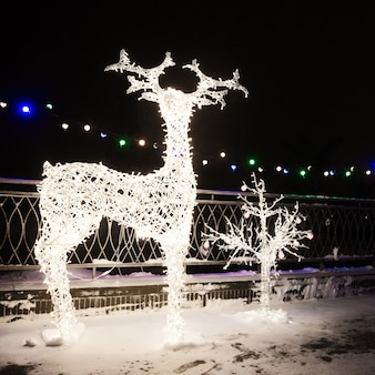 Veel feestelijke lichten lampen in vorm herten in avond nacht feestelijke verlichting. decoratieve stratenelementen in het kerstvakantieseizoen