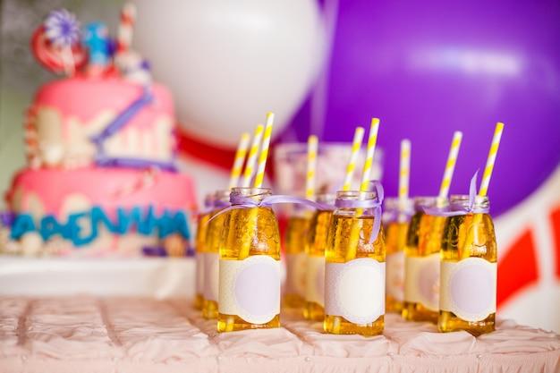 Veel flessen appelsap, speciale etiketten erop, witte en gele rietjes, grote roze cake en witte en paarse ballonnen