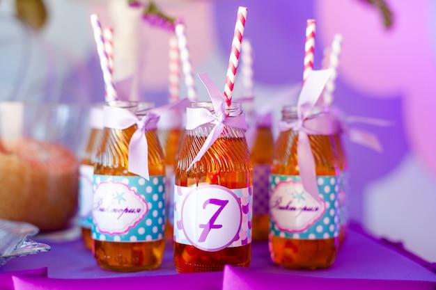 Veel flessen appelsap, speciale etiketten erop, witte en roze rietjes