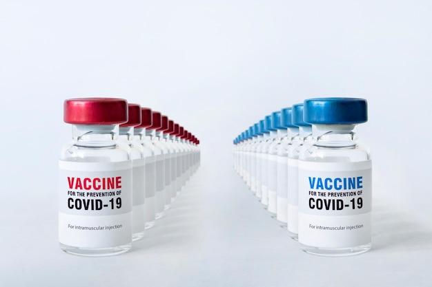 Veel flessen covid 19 coronavirusvaccin op de witte tafel. de medische opvatting van de bestrijding van de covid-19-pandemie. massaproductie van vaccins.