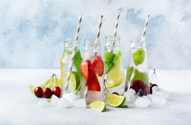 Veel flessen met verfrissende zomerlimonade met limoen, aardbei, kers, komkommer en ijs op een grijze betonnen achtergrond.